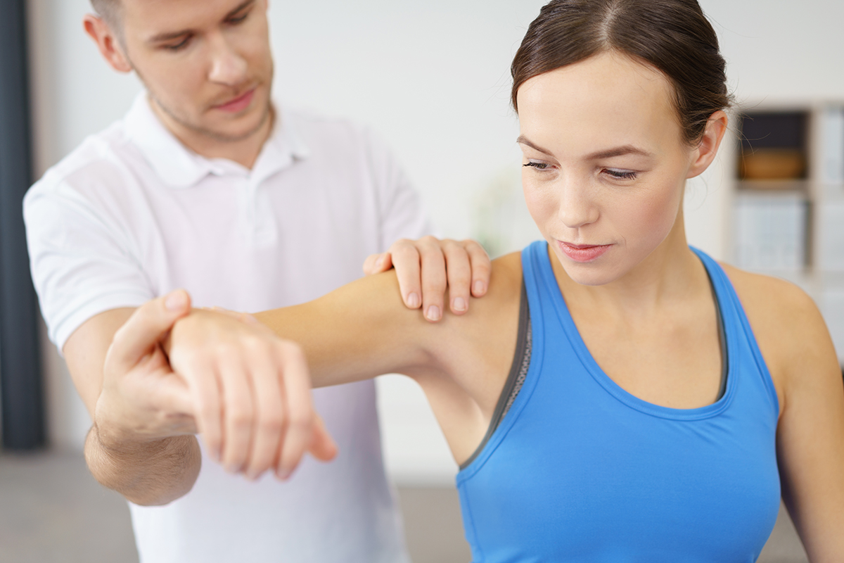 a man performing physiotherapy on a woman's hand