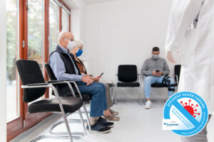 Senior couple with face masks sitting in a waiting room of a hospital
